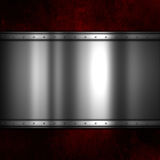 Shiny metal plate on a red grunge background Royalty Free Stock Photo