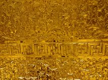 Shiny metal relief - probably gold - in buddhist temple of Ninh royalty free stock photo