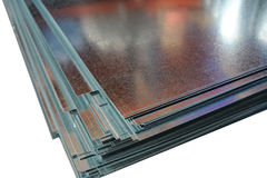 Shiny metal sheets corner. Folded stack of shiny metallic sheets closeup at white background Stock Photo