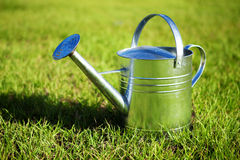 Shiny metal watering can in the grass Stock Photography