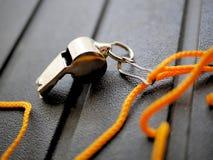 Shiny metal whistle with bright orange lanyard. stock photography
