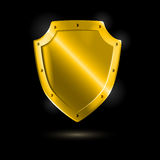 Shiny metallic golden shield on black Royalty Free Stock Images