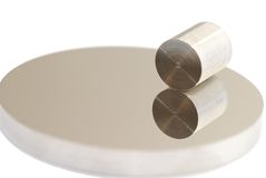 Shiny metals. Machined alloy cylinder on a flat round polished alloy surface Royalty Free Stock Photos