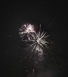 Shiny natural fireworks. On dark black sky background with a little smoke Royalty Free Stock Photography