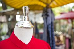 Shiny new Mannequin head over blurred outdoor market. Fashion and shopping traditional Thai style cloth Royalty Free Stock Photos