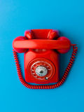 Shiny new red phone. Top view of red vintage phone on blue background stock images