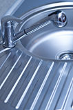 Stainless Steel Sink and Faucet. Shiny new stainless steel and chrome faucet, sink and drain board in shades of blue Stock Images