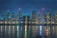 Shiny night cityscape on riverbank Royalty Free Stock Photo