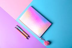 Shiny notebook with pink pompom and pens on color background. Flat lay royalty free stock photo