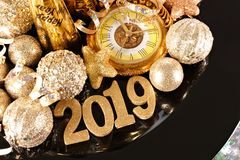 Shiny 2019 numbers with gold New Years decor on a black background royalty free stock image