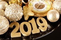 Shiny 2019 numbers with gold New Years decor, close up on a black background royalty free stock photo