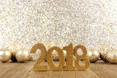 New Years Eve 2018 numbers with baubles and glittery background. Shiny 2018 numbers with golden baubles and glittery background, New Years Eve concept Stock Image