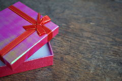 Shiny opened pink gift box with red ribbon and golden stitching on the wooden background Royalty Free Stock Photo