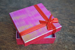 Shiny opened pink gift box with red ribbon and golden stitching on the wooden background Stock Images