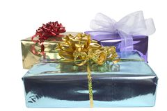 Shiny Parcels. Three mettalic foil parcels with gold & red Bows Royalty Free Stock Photos