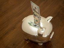 Piggy Bank Accepting a Hundred Dollar Bill. A shiny piggy bank with reflections photgraphed from above with a shallow depth of field. A hundred dollar bill is royalty free stock photography