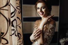 Beautiful brunette stylish bride getting ready in the morning in. Shiny portrait of beautiful bride standing before the window Stock Image
