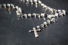 Shiny and pretty Rosary on a black surface. Cross and Hail Mary Pendant. Royalty Free Stock Photo