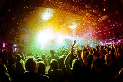 Shiny rainbow confetti during the concert and the crowd silhouettes with their hands up. Shiny rainbow confetti during the concert and the crowd of people royalty free stock photography