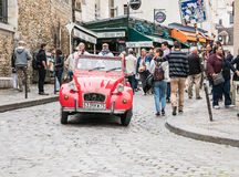 Shiny red antique Citroen makes way through Montmartre crowd, Pa Royalty Free Stock Image