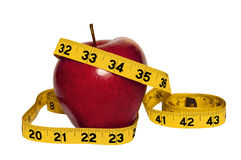 Red apple and measuring tape. A shiny red apple with a yellow measuring tape marked in inches wrapped around it, white background Royalty Free Stock Photo