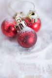 Shiny red Christmas balls over snow background Royalty Free Stock Photos
