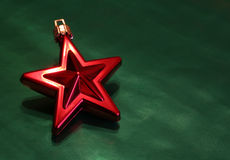 Shiny Red Christmas Star. A shiny red Christmas star ornament sitting on green wrapping paper Royalty Free Stock Image