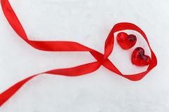 Shiny red glass hearts with ribbon on the snow Royalty Free Stock Photos