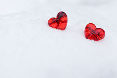 Shiny red glass hearts on the snow Stock Image