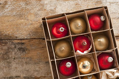 Shiny red and gold holiday ornaments in box Royalty Free Stock Photo