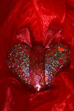 Shiny red heart. Red, shiny heart on the red organdie background Royalty Free Stock Photos