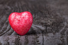 Shiny red heart on old wooden background Stock Photo