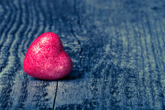Shiny red heart on old wooden background. Toned Stock Photo