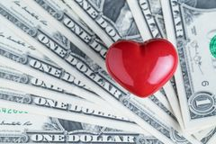 Shiny red heart on pile of US Dollar banknotes using as business Royalty Free Stock Image