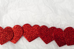 Shiny red hearts on white paper Stock Photos