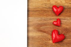 Shiny red hearts on wooden background. With empty white card Stock Images