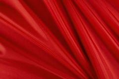 Shiny red material. Close up shot of shiny, red, wavy fabric Stock Image