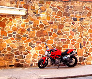 Shiny Red Motorcycle Parked By Stone Wall. A shiny, fast, red motorcycle is parked in front of an old stone wall in an alley Royalty Free Stock Photos