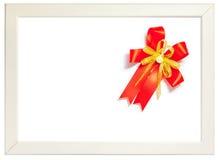 Shiny red ribbon bow decorated on white photo frame, season gree Royalty Free Stock Image
