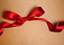 Shiny red satin ribbon on golden background Stock Images