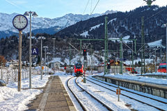 Shiny red train arriving at Garmisch-Partenkirchen railway stati Stock Images