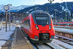 Shiny red train stopped at the Garmisch-Partenkirchen railway st Stock Photos