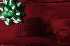Shiny red wrapping paper with green bow Royalty Free Stock Images