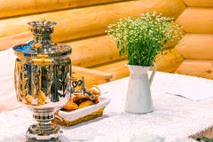 Shiny samovar and bouquet of flowers Stock Photo