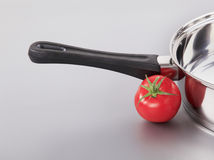 Shiny saucepan and a red tomato Stock Image