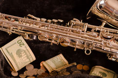 Shiny saxophone lying across open instrumental casing with black velvet interior and pile of money inside.  Royalty Free Stock Image