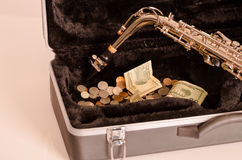 Shiny saxophone lying across open instrumental casing with black velvet interior and pile of money inside.  Stock Image