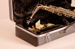 Shiny saxophone lying across open instrumental casing with black velvet interior and pile of money inside.  Stock Images