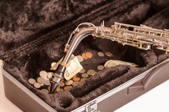 Shiny saxophone lying across open instrumental casing with black velvet interior and pile of money inside.  Royalty Free Stock Photography