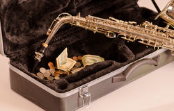 Shiny saxophone lying across open instrumental casing with black velvet interior and pile of money inside.  Royalty Free Stock Images